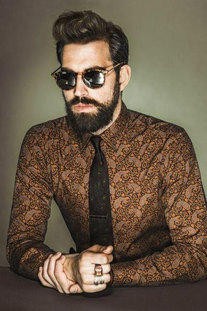 Homem recostado em uma bancada com roupa social, gravata, óculos escuro, barba média e cabelo arrepiado no estilo anos 80.