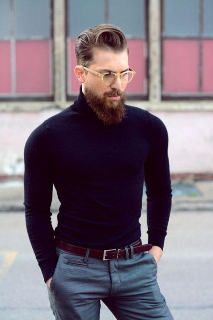 Homem usando uma blusa de gola rolê com um óculos, barba cheia e cabelo grande penteado para trás.