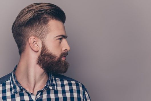 Homem de perfil com cabelo jogado para trás e barba pequena, mas volumosa e bem feita.
