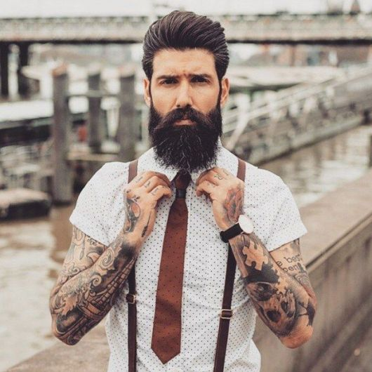 Homem tatuado arrumando as golas de sua camisa social com suspensórios, relógio e uma gravata. Seus cabelos são longos e penteado para trás e sua barba é grande e volumosa com pequenos fios grisalhos.