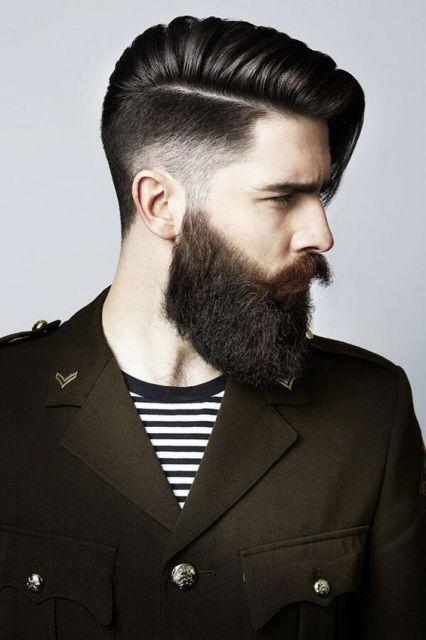 Homem de perfil com cabelo grande bem penteado para o lado e uma barba grande volumosa.