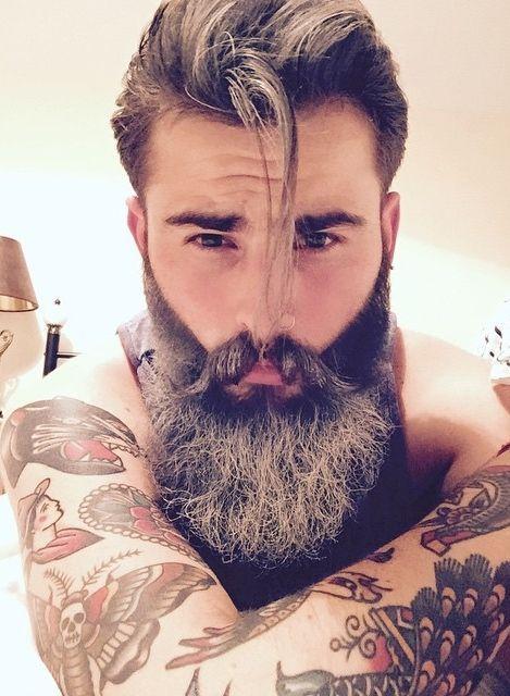 Homem com cabelo grande bem penteado, muitas tatuagens e uma barba grande bem feita com bastante fios grisalhos.