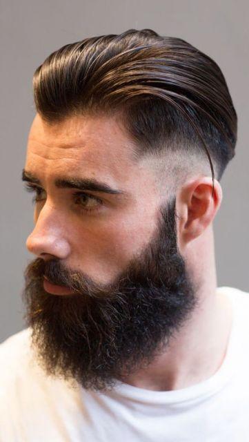 Homem de perfil com um undercut bem penteado e barba volumosa bem feita.