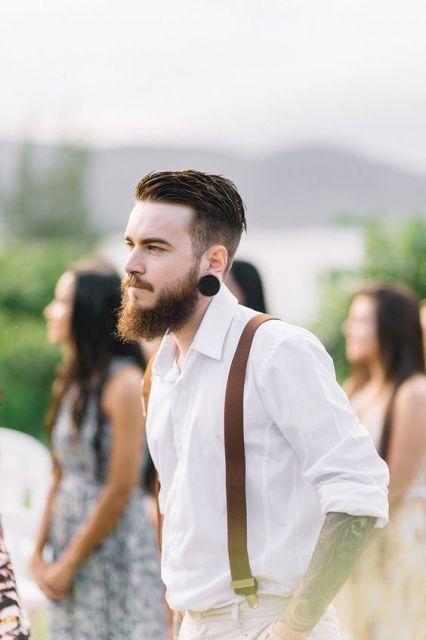 Homem de social e suspensórios com alargador, undercut e barba ruiva média bem aparada.