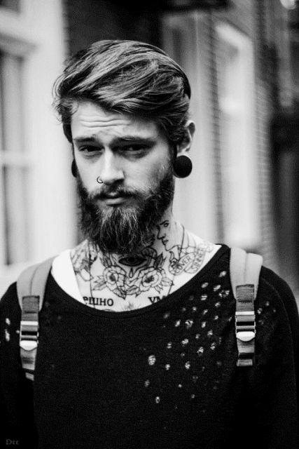 Homem com uma mochila, muitas tatuagens no pescoço, alargador grande e uma barba média bem cuidada.
