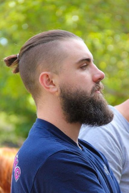 Homem de perfil usando um coque raspado nas laterais e uma barba média bem volumosa.