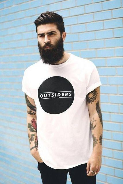 Homem tatuado com as mãos nos bolsos, cabelo bem penteado com gel e uma barba média, mas muito volumosa e bem aparada.
