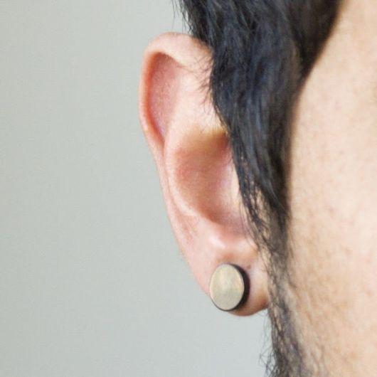 Foto tirada de perto da orelha de um homem com um alargador de pressão.