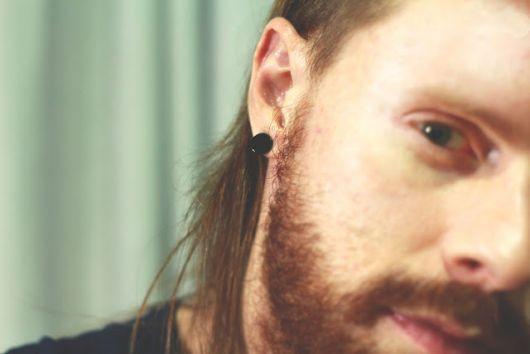 Foto da metade do rosto de um homem com cabelos longos, barba e um alargador preto de pressão.