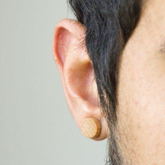 Foto tirada próxima da orelha de um homem usando um alargador de pressão de madeira.