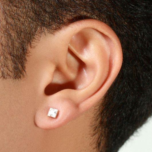 Foto em close up da orelha de um homem usando um brinco de pressão masculino discreto.