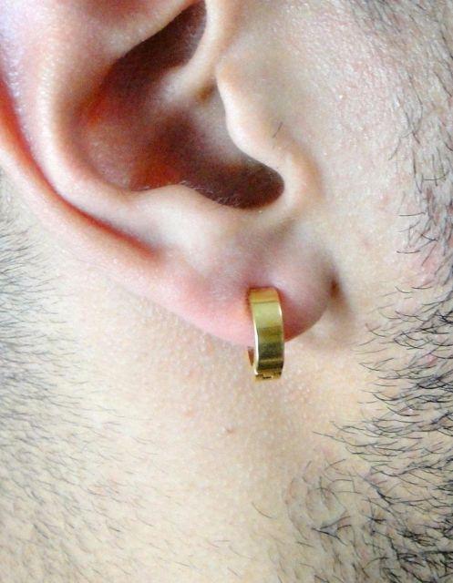Foto em close up da orelha de um homem usando um brinco de pressão masculino dourado.