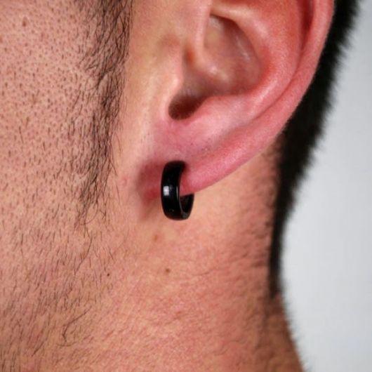 Foto em close up da orelha de um homem usando um brinco de argola de pressão preto.