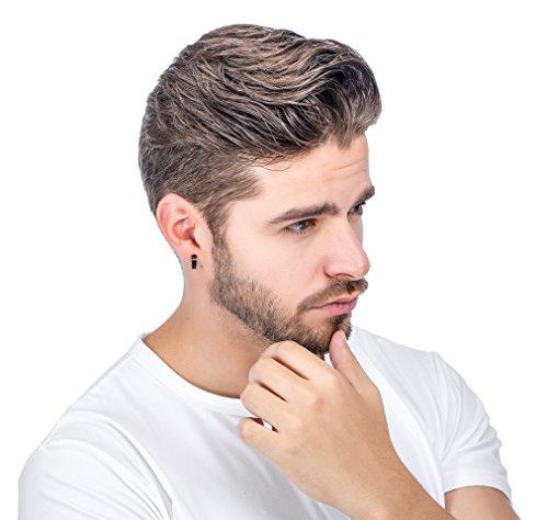 Homem em posição pensativa todo vestido de branco com um pequeno brinco de pressão de argola preto.