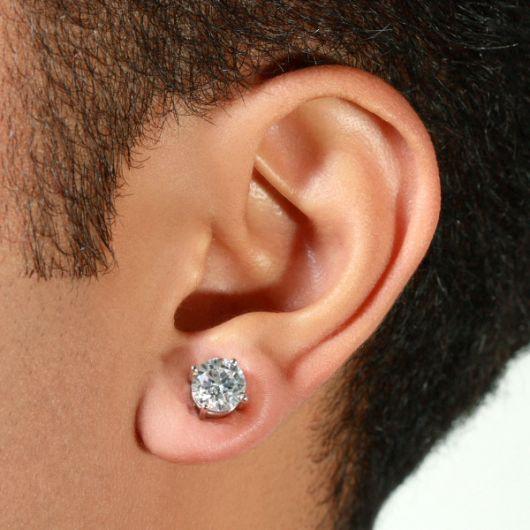Foto em close up da orelha de um homem com um brinco de pressão brilhante.