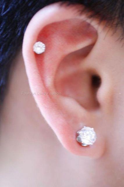 Foto em close up da orelha de um homem que está usando um brinco de prssão brilhante e um piercing brilhante na mesma orelha.