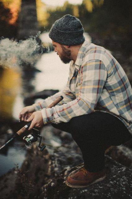 Homem com camisa de flanela e touca sentado em um pedra de frente a um rio enquanto pesca.
