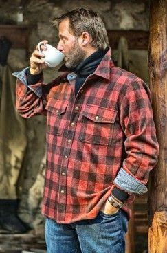 Homem com camisa xadrez vermelha com uma mão no bolso enquanto bebe uma xícara de bebida quente..