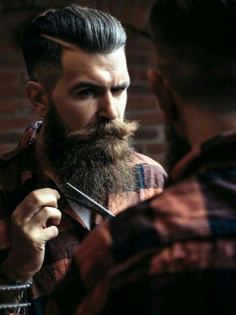 Homem com cabelo bem penteado para trás enquanto segura uma tesoura perto de sua barba.