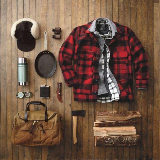 Diversas peças de vestuário do estilo lenhador colocadas em um solo de madeira.