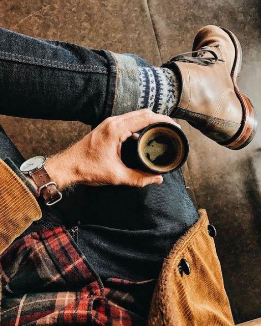 Foto de uma mão segurando uma xícara de café com as pernas cruzadas e uma bota no pé