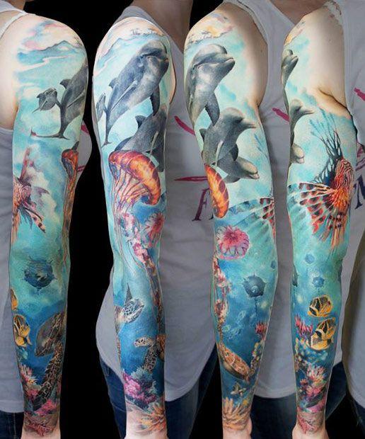 Braço fechado com a tatuagens do fundo do mar, onde vemos um grupo de golfinhos ao topo nadando em grupo.