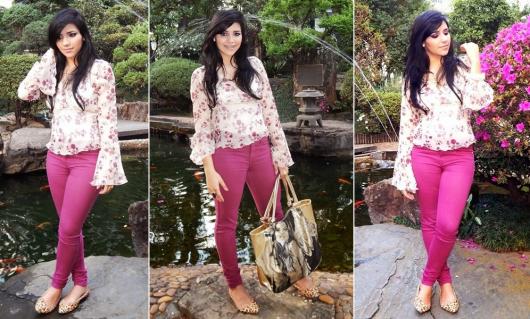 Modelo usa calça roxa, camisa manga longa floral e bolsa de mão.