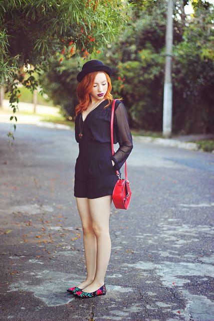Modelo veste macaquinho preto com bolsa vermelha.