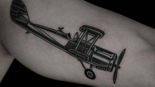 Tatuagem da lateral de um avião antigo com um único assento e movido a hélices dianteiras.
