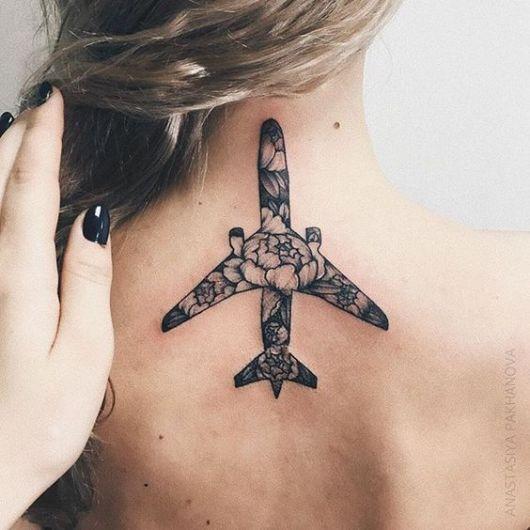 Tatuagem de um avião preenchido com diversas flores no centro das costas de uma mulher.