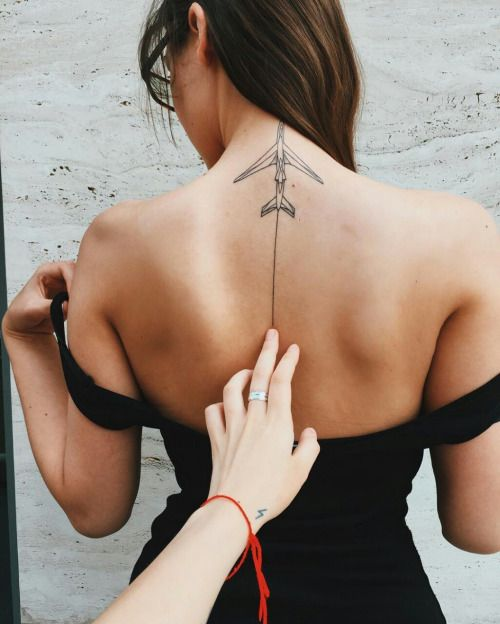 Tatuagem de um avião feito no centro superior das costas de uma mulher. Ele deixa um rastro que desce ao longo do centro de suas costas.