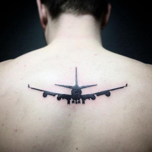 Tatuagem de silhueta de um avião decolando preenchido de preto no centro das costas de um homem.