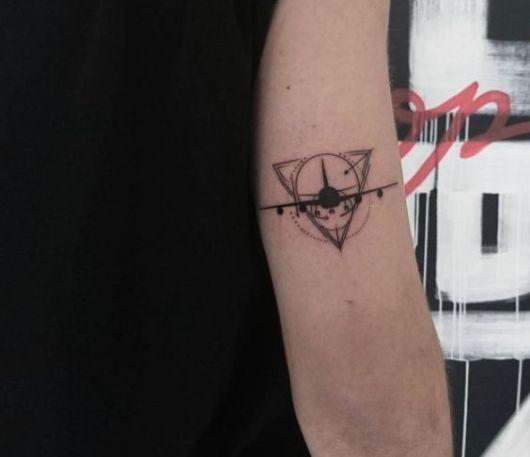 Tatuagem feia acima do cotovelo com a silhueta de um avião decolando dentro de um circulo que está inserido em um triângulo.