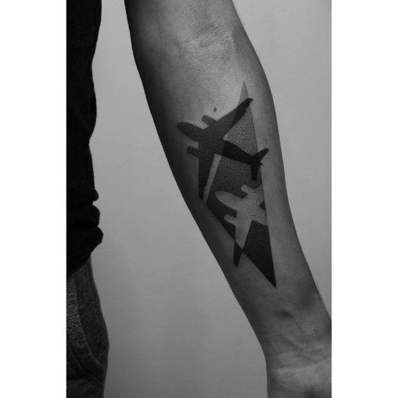Tatuagem geométrica da sombra de um avião que é projetada dentro de um triângulo feito a partir de pontilhismo.