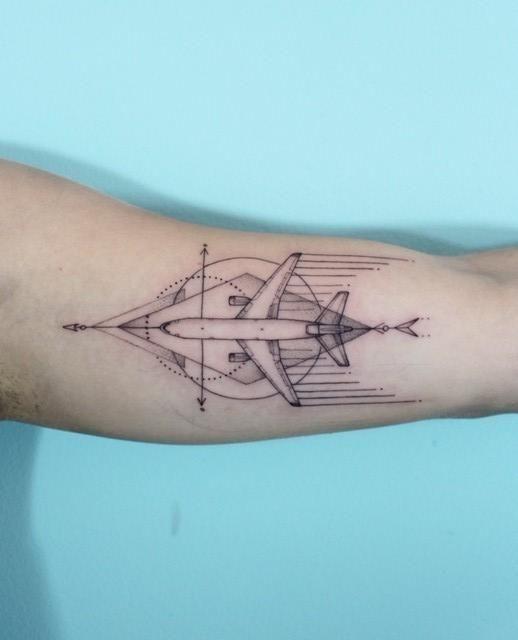 Tatuagem de um avião visto de cima sincronizado com um losango no qual está inserido.