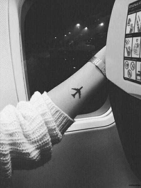 Tatuagem delicada do contorno de um avião preenchido de preto feita no antebraço de uma pessoa que está dentro de um avião.