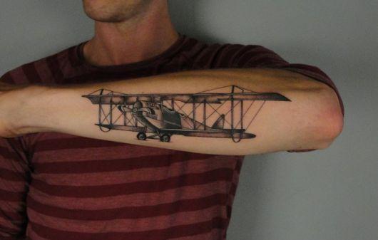 Tatuagem de um avião de modelo antigo feito na parte de fora do antebraço de um homem.