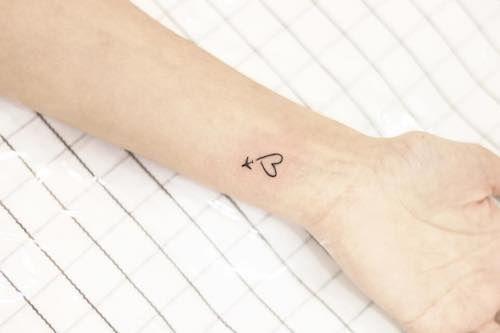 Tatuagem delicada no pulso de um avião voando e deixando um rastro que forma um coração.