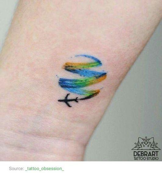 Tatuagem delicada no pulso de um avião voando enquanto deixa um rastro que é feito com aquarela.