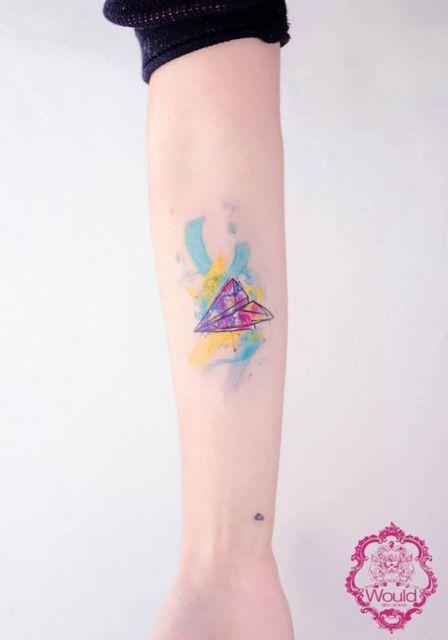 Tatuagem de um avião de papel simples feita no antebraço com detalhes também coloridos ao seu redor.