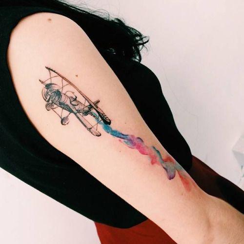 Tatuagem de um avião com antigo com hélice dianteira decolando e deixando um rastro de fumaça feito com aquarela.