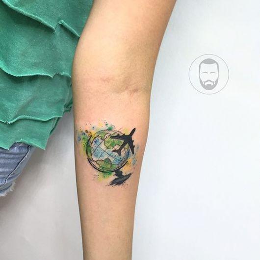 Tatuagem da silhueta de um avião sobrevoando o globo terrestre colorido a partir de cores de aquarela.