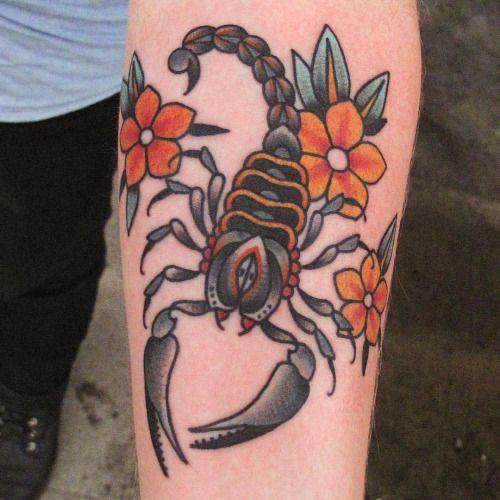 Tatuagem de escorpião no braço feita no estilo old school com traços e cores vivas.