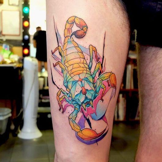 Tatuagem na coxa de um escorpião pintado com diversas cores diferentes e um pouco de aquarela.