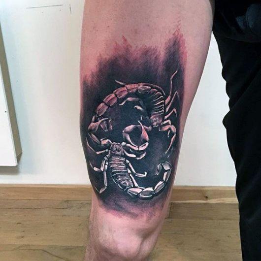 Tatuagem feita na coxa de dois escorpiões em se encarando com um fundo escuro.