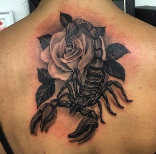 Tatuagem de um escorpião realista nas costas com uma rosa ao fundo.