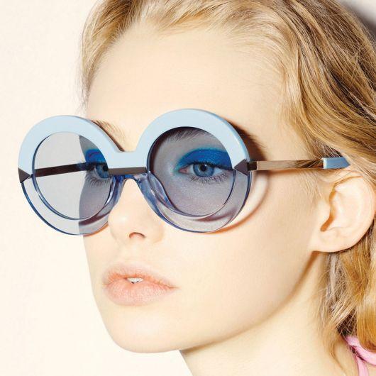 Modelo de cabelos presos usa óculos de sol azul com armação azul bebe.