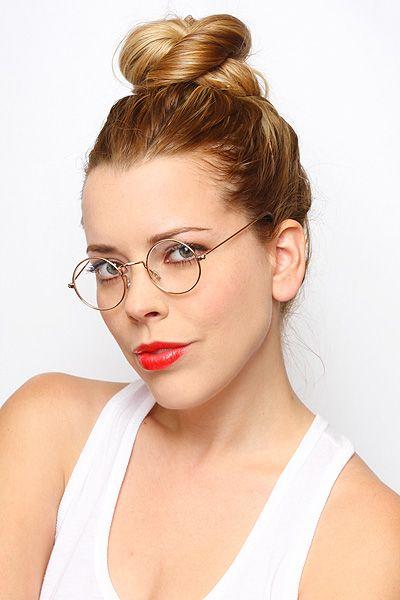 Modelo usa cabelo preso, batom vermelho, blusa regata branca e óculos com lentes transparentes.
