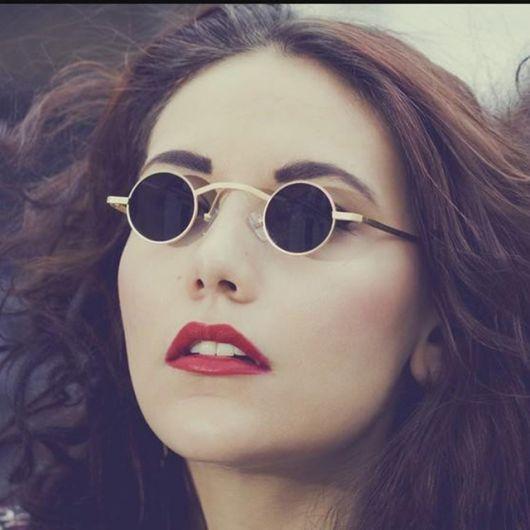 Modelo usa cabelo solto e óculos com lentes pequenas e armação dourada.