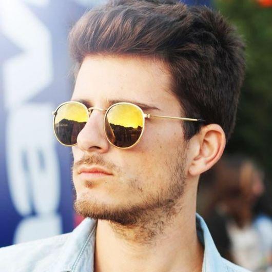 Modelo usa camisa jeans azul com óculos redondo masculino espelhado amarelo.